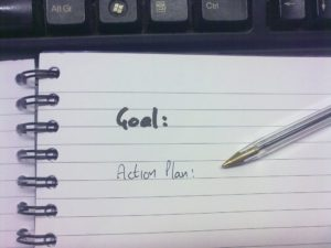 Image of notebook with written text - goal and action plan