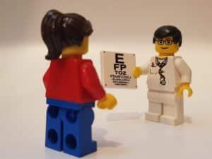2 lego minifigures, one having an eye test with eye chart